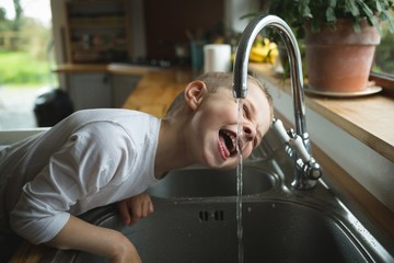 Boy drinking water from faucet in kitchen