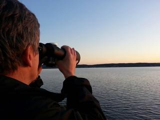 Man with binoculars searching the ocean