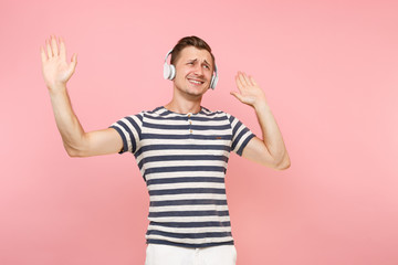 Portrait of smiling young man wearing striped t-shirt listening to music with white wireless headphones, enjoy isolated on trending pastel pink background. People sincere emotions lifestyle concept.