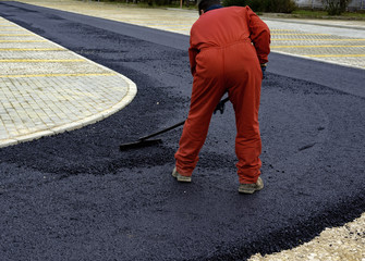 Worker distributes on the edge the asphalt laid out for the construction of a road
