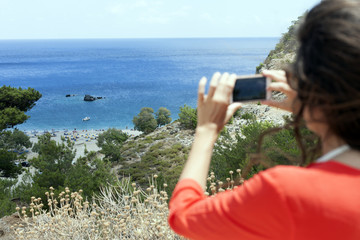 Greek island, young woman taking a panorama photo of the beach with mobile phone