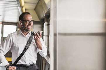 Laughing businessman on a ferry with cell phone and earphones