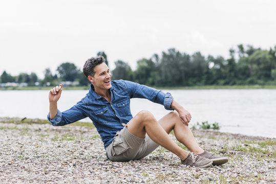 Laughing man sitting at the riverside throwing stones