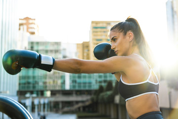 Sportive young woman boxing in the city