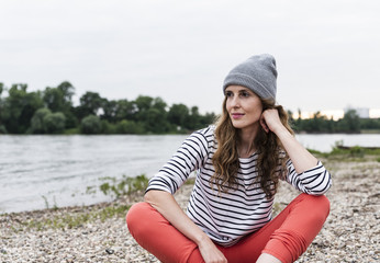 Portrait of woman wearing wooly hat sitting at the riverside