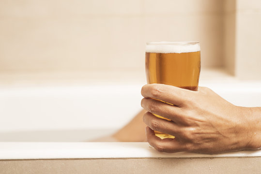young man drinking a beer on the bathtub