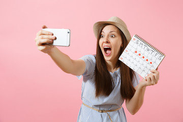 Excited woman in blue dress doing selfie on mobile phone, holding periods calendar for checking menstruation days isolated on pink background. Medical, healthcare, gynecological concept. Copy space.
