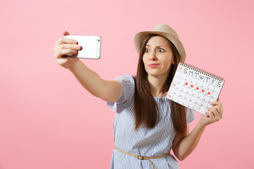 Confused woman in blue dress doing selfie on mobile phone, holding periods calendar for checking menstruation days isolated on pink background. Medical, healthcare, gynecological concept. Copy space.