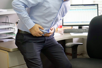 Close-up of office worker having painful stomachache. Chronic gastritis. Businessman with abdominal pain at his workplace in the office. Body And Health Care Concept.