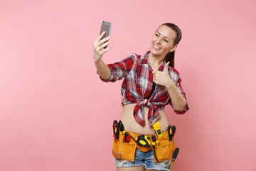 Strong excited young handyman woman in plaid shirt, denim shorts, kit tools belt full of instruments doing selfie on mobile phone isolated on pink background. Female in male work. Renovation concept.
