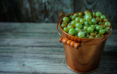 Close up yellow brass bucket with berry of green gooseberry stand in right side on vintage wood background. Top view