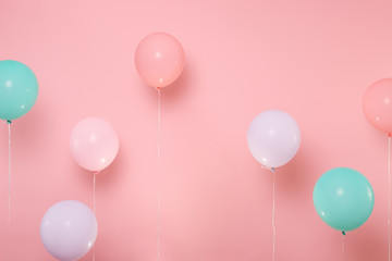 Colorful air balloons on pastel bright trending pink background. Decoration for birthday holiday party concept.