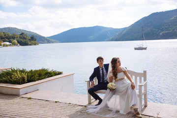 A stylish young bride and groom in a white lavish wedding dress are sitting on a bench in front of a river and hills.