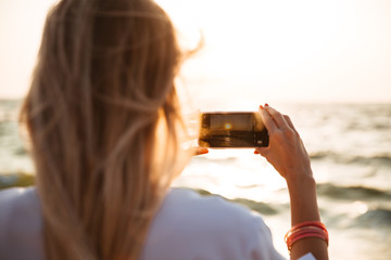 Back view of a young girl taking a picture of a sunset