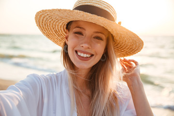 Delighted young girl in summer hat and swimwear