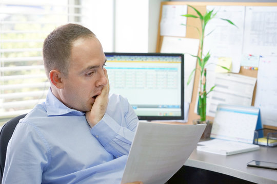 Office worker man reading negative news in letter. Shocked businessman. Business manager received layoff message letter from company feeling surprised. An agitated male without joy.
