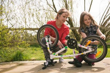 Mother and daughter repairing bicycle at backyard