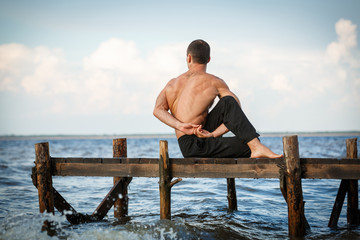 Young yoga trainer practicing ardha matsyendrasana or lord of the fishes pose on a wooden pier on a sea or river shore