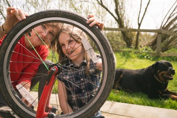 Mother and daughter repairing bicycle together