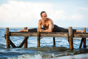 Young yoga trainer practicing split  exercises on a wooden pier on a sea or river shore.