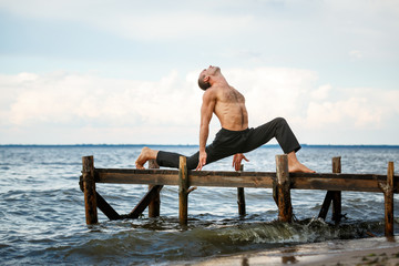 Young yoga trainer practicing yoga exercises on a wooden pier on a sea or river shore.