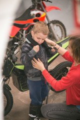 Mother preparing her son for bike riding