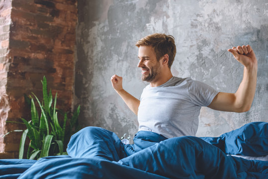 handsome young man stretching in bed during morning time at home