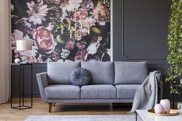 Real photo of dark living room interior with glass lamp, floral wallpaper, molding on wall and sofa with cushion