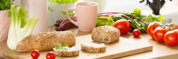 Close-up of bread on a cutting board with tomatoes and other vegetables around on a wooden kitchen table