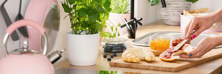 Woman's hands spreading jam on a croissant pastry and herbs and fruit on a countertop in a bright, natural kitchen interior