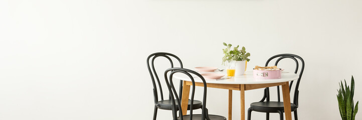 Springform cake pan and pastel pink plates on a wooden table with black chairs around in a white dining room interior with copy space