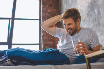 young man with headache holding glass of water in bed at home