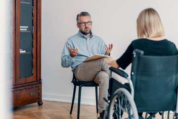 Counselor talking with disabled woman in the wheelchair in the office