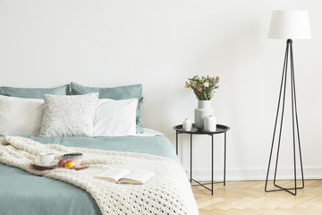 Bed with tea cup, apples and blueberries on breakfast tray and open book in real photo of bright bedroom interior with metal bedside table with flowers