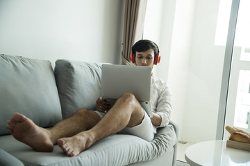 Happy man relaxing on the sofa listening to music with laptop at home