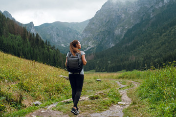 Rear shot of young brunette backpacker woman hiking on the green pathway in Tatra Mountains to Rysy peak . Poland, Slovakia