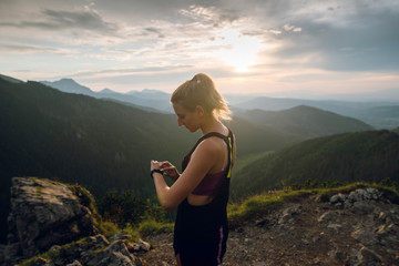 Side view of young sporty woman in sportswear using smartwatch while jogging in the mountains on sunset. High Tatra mountains