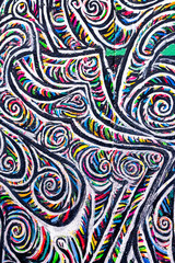A abstract colourful patter, black, white and rainbow on a wall