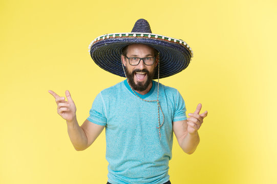 Celebrate traditions. Man on smiling face in sombrero hat celebrating, yellow background. Guy with beard looks festive in sombrero. Fest and holiday concept. Man in festive mood at party celebrating