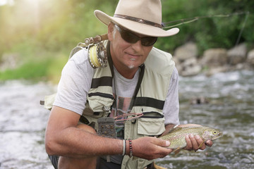 Fly fisherman catching rainbow trout in river