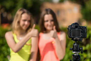 Two teenage girls, in summer in the park, are recording video on the camera. Blurred background free space for text.