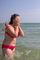woman washing her face in the sea