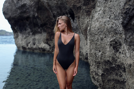 Beautiful girl in a black swimsuit in a blue lagoon among the rocks