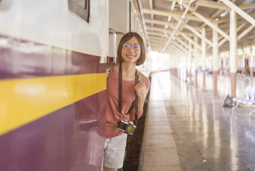 A lonely young woman travels her journey by train, at train station in Bankok,Thailand