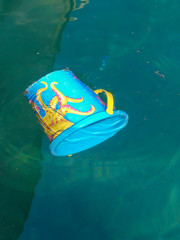 Dubrovnik, Croatia - August 7 2018: childs plastic bucket floating in sea causing pollution