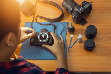 The photographer is cleaning his camera by himself. To keep the dust free and to prolong the life of the camera.