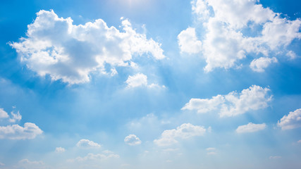 Wonderful blue sky with white clouds an sunrays as a background