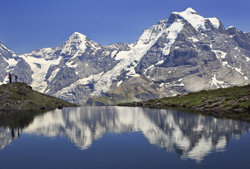 Photo sur Plexiglas Reflexion Summer in the Swiss Alps, Murren area, overlooking the Monch and Jungfrau mountains reflected in Grauseewli Lake, Canton of Bern, Switzerland, Europe