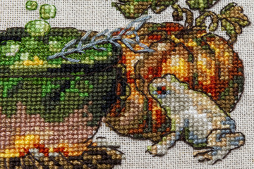 Cross-stitch embroidery with cat in hat, cauldron, toad, bonfire and pumpkin.