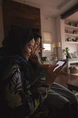 Muslim mother and daughter using digital tablet